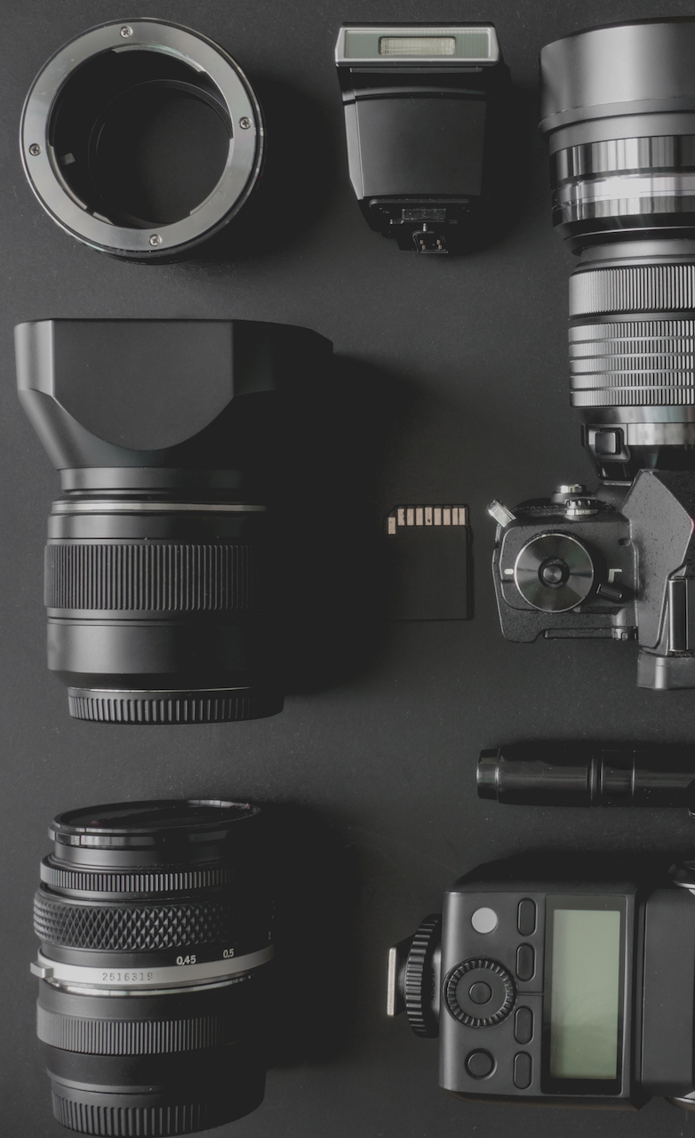 top view of work space photographer with mirrorless camera system camera flash battery charger camera cleaning kit memory card and camera accessory on black table background